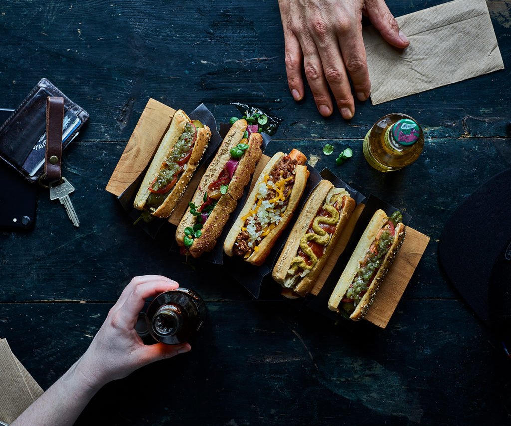 4 hot dogs with toppings, two hands in frame