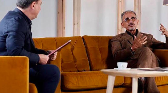 Jeffrey Young interviewing Kamal Bengougam for The Global Coffee Festival. Sitting on a yellow couch with coffee in the foreground.